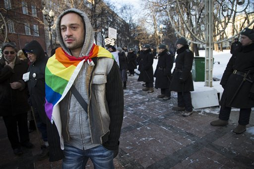 "Credit: AP - In this Sunday, Jan. 19, 2014 file photo a Russian gay rights activist walks along a police line during a rally at a Moscow boulevard. When the Sochi Winter Olympics begin on Friday, Feb. 7, 2014, many will be watching to see whether Russia will enforce its law banning gay ""propaganda"" among minors if athletes, fans or activists wave rainbow flags or speak out in protest. The message so far has been confusing. (AP Photo/ Alexander Zemlianichenko, file)"