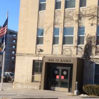 The New York flag billows outside the Ithaca Hall of Justice. Will college programs appear in NY state prisons in the future?